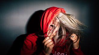 Puber met adhd en een rode capuchontrui op die schreeuwt