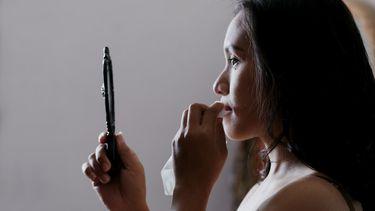vrouw kijkt naar zichzelf in de spiegel