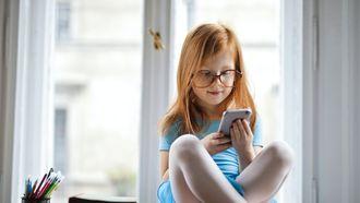 Kind dat een telefoon vasthoudt en voor het raam zit