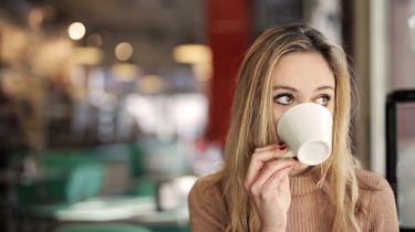 Vrouw die koffie drinkt en zich afvraagt waarom ze nu moet poepen