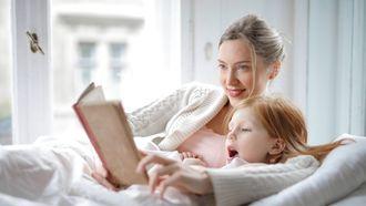 voorlezen / moeder en kind lezen een boek in bed