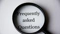 Een vergrootglas over tekst met Frequently Asked Questions
