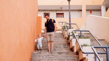 Vader die zijn dreumes helpt bij het leren traplopen op vakantie