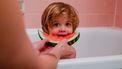 peuter eet watermeloen in bad
