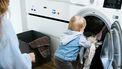 Kindje die de was in de wasmachine doet, terwijl haar ouders deze moeten schoonmaken omdat hij stinkt