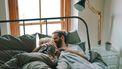 vrouw die met haar man in bed ligt en minder zin heeft in seks tijdens haar zwangerschap omdat het anders voelt