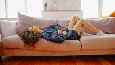 menstruatie / vrouw ligt op de bank met kramp in buik