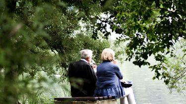 ouders zitten op een bankje in de natuur