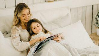 vrouw leest dochtertje voor