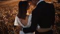 Bruidspaar op de foto in een veld voor hun trouwreportage