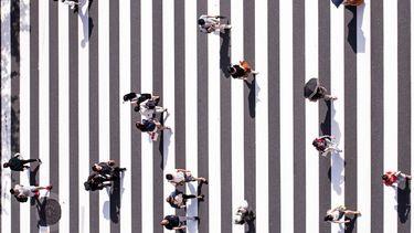 mensen lopen over een zebrapad