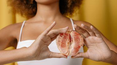 Vrouw die een grapefruit vasthoudt wat symbool staat voor vaginale problememen