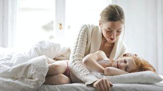 Moeder die haar dochter naar bed brengt op haar vaste bedtijd
