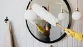 Man die de badkamer schoonmaakt aan de hand van schoonmaaktips voor luie mensen