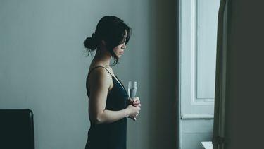 Vrouw met glas champagne die uit het raam kijkt