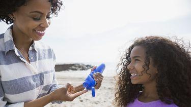 vrouw smeert zonnebrandcrème op gezicht van kind
