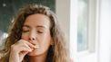 Vrouw eet een donut met haar ogen dicht, en is waarchijnlijk aan het emo-eten