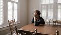 Vader van autistische zoon die met zijn handen in het haar aan tafel zit