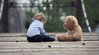 Jongetje die met zijn beer op de grond zit en niet wil dat zijn knuffel gewassen wordt