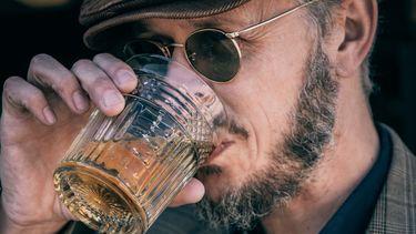 man drinkt whiskey