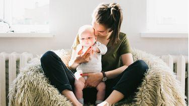 vrouw met baby in haar armen die volgens haar sterrenbeeld de leukste tante is