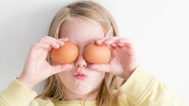 kind met eieren voor haar ogen tijdens het koken