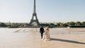 Net getrouwd koppel voor de Eiffeltoren zeggen romantische zinnetjes in andere talen tegen elkaar