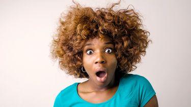 Vrouw die gestrest is en verrast in de camera kijkt