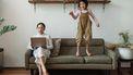 Kind dat weinig zelfbeheersing heeft en op de bank springt naast haar werkende moeder
