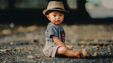 Schattige baby in leuke babykleertjes zittend op straat