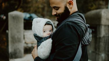 Vader met baby in draagzak die checkt of de temperatuur van de baby niet te warm of te koud is