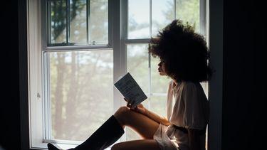 Vrouw zit op vensterbank te lezen en is eenzaam