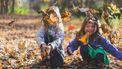 Kinderen die buiten spelen met herfstbladeren en geen behoefte hebben aan meer