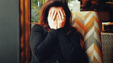 vrouw die haar handen voor haar gezicht houdt omdat ze zich kapot schaamt om de gênante uitspraken van haar kinderen
