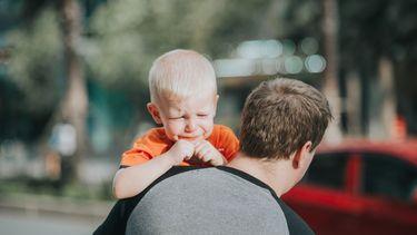Huilende jongen die opgetild wordt door zijn vader